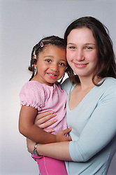 Young mother holding daughter smiling,