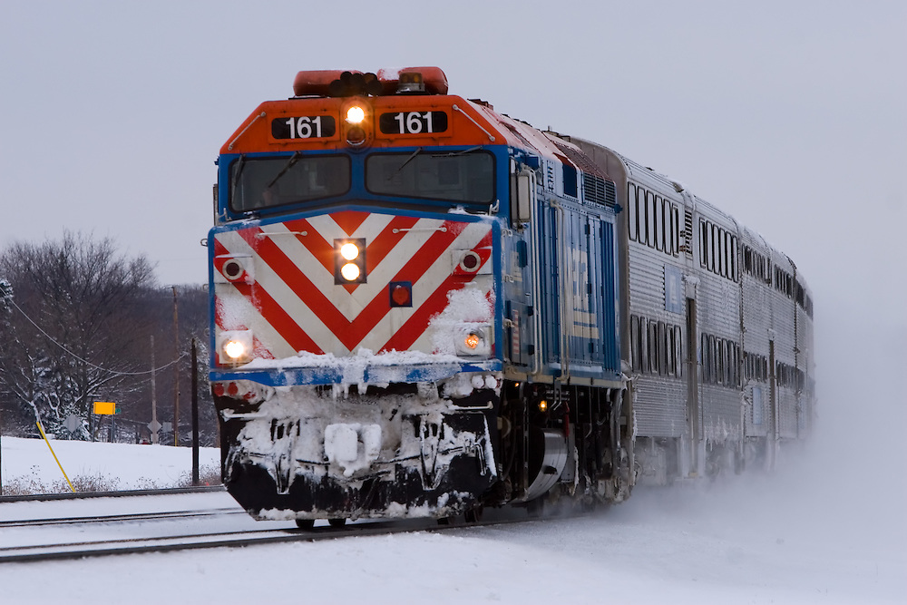 A Metra commuter train speeds through a fresh blanket of snow in suburban Chicago, IL.