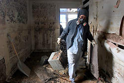 21December 2005. New Orleans, Louisiana. Post Katrina aftermath.<br /> Armand Devezin clears his grandfathers' devastated, mould filled house in the 9th Ward long after the  flood from Hurricane Katrina subsided. The house has only recently been refurbished and has seen water to the ceilings before when Hurricane Betsy hit in the 1960's.<br /> Photo; ©Charlie Varley/varleypix.com