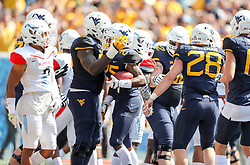 Sep 16, 2017; Morgantown, WV, USA; West Virginia Mountaineers running back Justin Crawford (25) celebrates with teammates after scoring a touchdown during the first quarter against the Delaware State Hornets at Milan Puskar Stadium. Mandatory Credit: Ben Queen-USA TODAY Sports