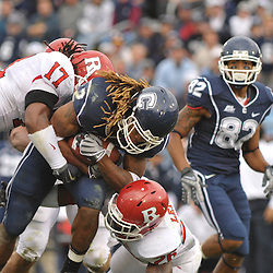 Oct 31, 2009; East Hartford, CT, USA; Rutgers linebacker Damaso Munoz (17) and cornerback Joe Lefeged (26) tackle Connecticut running back Andre Dixon (2) during second half Big East NCAA football action in Rutgers' 28-24 victory over Connecticut at Rentschler Field.