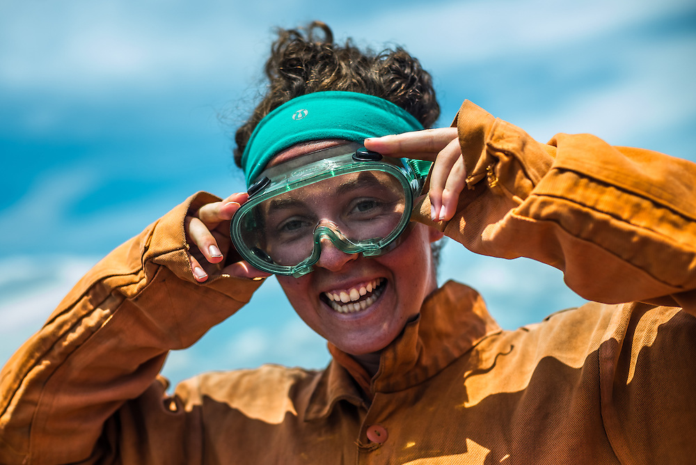 LEON, NICARAGUA - SEPTEMBER 18, 2014: Jade Cadoret, 20, a tourist from Canada, gears up in an orange jumpsuit and green goggles in preparation to board down Cerro Negro volcano. The jumpsuits are used for protective measures, because boarders reach high speeds of up to 95kilometers/hour and the rough surface at such high speeds can easily damage their skin. Guided tours are available from $29 USD to board down the volcano, located an hour outside of Leon. PHOTO: Meridith Kohut