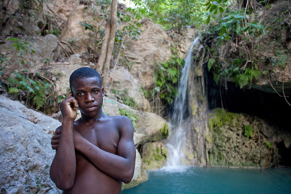 A boy stands in front of a waterfall cascadeing down rocks into a pool near a spring providing a rare source of fresh water in Ile de La Gonave, Haiti