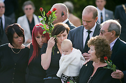 © licensed to London News Pictures. 08/09/2011. Brize Norton, UK. Joanne Weston (centre) wife of Sergeant Barry Weston holding her daughter Rose surrounded my family and friends as the coffin of Sergeant Barry Weston of 42 Commando Royal Marines passes through the town of Carterton, Oxfordshire today (08/09/2011). Today was the first time a repatriation had passed through RAF Brize Norton. Sgt Weston was killed on August 30 while leading a patrol near the village of Sukmanda in southern Nahr-e Saraj, Helmand province. Photo credit: Ben Cawthra/LNP