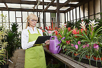 Senior florist using tablet pc in greenhouse