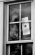 Jonathan McLaughlin, 3, looks out the window in which hangs a flag for his father Timothy McLaughlin, who is a Major with the 50th Support Battalion of the New Jersey National Guard headed to Iraq.