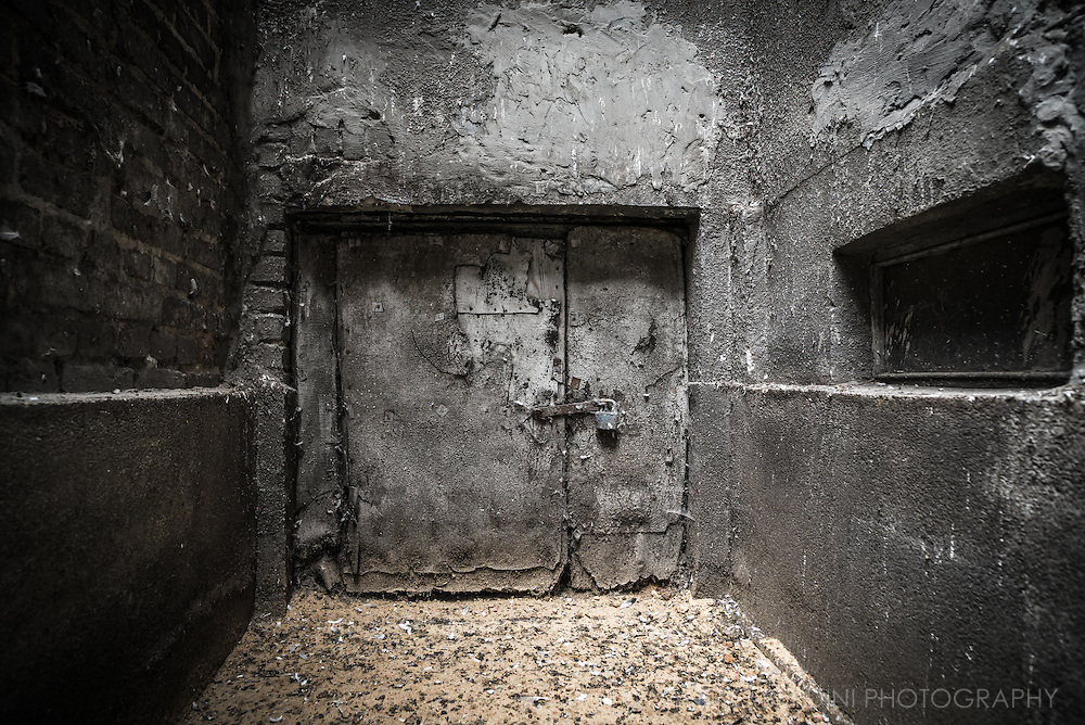 An old basement door in the courtyard of one of the few remaining buildings that survived the destruction of the city operated by the Nazi force.