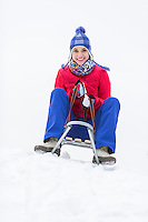 Full length portrait of happy young woman enjoying sled ride in snow