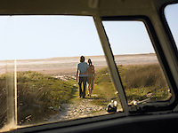 Couple walking away from camper van towards beach view through camper van window