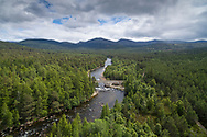 The river dee midstream at the Bridge of Dee with pine forest either side.  Cairngorms National Park, Scotland.