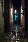 Lamps reflecting on stone cobbles at night in cobbled street alleyway in Erice, Sicily, Italy