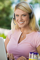 Woman Using Laptop Wearing Headset