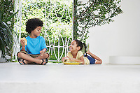Boy and girl (5-6 years) eating on verandah floor