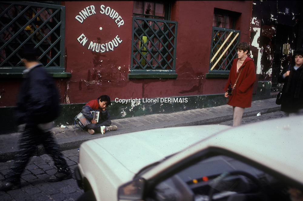 Gypsy boy begging with his accordion, Montmartre, Paris, France. Kodachrome