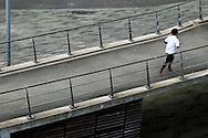 Nederland,  Rotterdam, 2 febr 2014<br /> Vrouw jogt over een brug die naar de Erasmusbrug gaat<br /> Foto: Michiel Wijnbergh