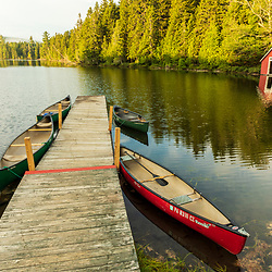 Canoes at a dock in Island Pond at Red River Camps in Aroostook County, Maine. Deboullie Public Reserve Land.