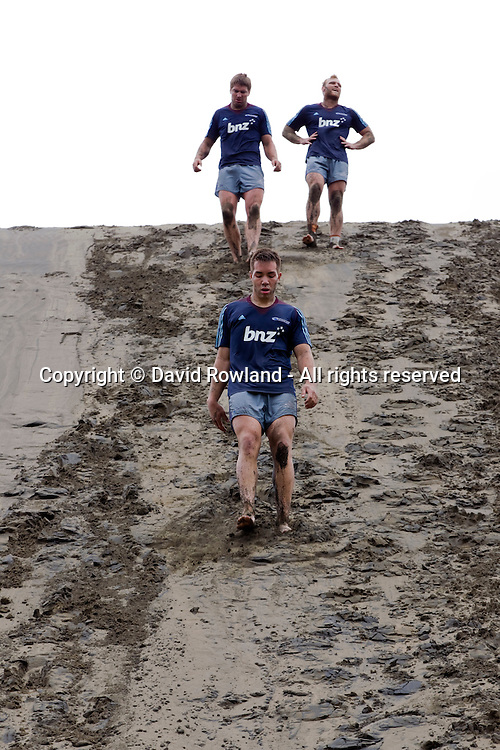 Albert Nikoro, leads Tim Perry and Luke Braid down the sand dunes at the Blues rugby training session, Bethells Beach, Auckland, New Zealand, Saturday, December 22, 2012. Photo: David Rowland/PHOTOSPORT
