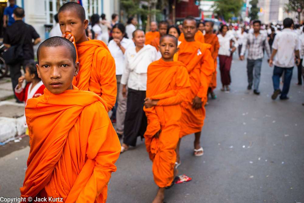 "03 FEBRUARY 2013 - PHNOM PENH, CAMBODIA:   Novice Buddhist monks walk down the street to the final Buddhist chanting service for former Cambodian King Norodom Sihanouk in the crematorium built for the King's funeral at the National Museum in Phnom Penh. Norodom Sihanouk (31 October 1922 - 15 October 2012) was the King of Cambodia from 1941 to 1955 and again from 1993 to 2004. He was the effective ruler of Cambodia from 1953 to 1970. After his second abdication in 2004, he was given the honorific of ""The King-Father of Cambodia."" He served as puppet head of state for the Khmer Rouge government in 1975-1976, before going into exile. Sihanouk's actual period of effective rule over Cambodia was from 9 November 1953, when Cambodia gained its independence from France, until 18 March 1970, when General Lon Nol and the National Assembly deposed him. Upon his final abdication in 2004, the Cambodian throne council appointed Norodom Sihamoni, one of Sihanouk's sons, as the new king. Sihanouk died in Beijing, China, where he was receiving medical care, on Oct. 15, 2012. His cremation will take place on Feb. 4, 2013. Over a million people are expected to attend the service.   PHOTO BY JACK KURTZ"