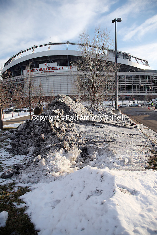 The Sports Authority Field at Mile High stadium stands tall in the background with mounds of snow piled up in the foreground in this wide angle, general view photograph taken before the Cincinnati Bengals 2015 NFL week 16 regular season football game against the Denver Broncos on Monday, Dec. 28, 2015 in Denver. (©Paul Anthony Spinelli)