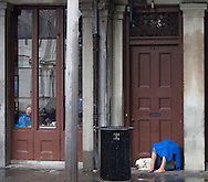 A man and his dog sleep on Jackson Square, French Quarter, New Orleans on a rainy Sunday, August 19, 2012, while a patron at a restaurant peers from the window to St. Louis Cathedral.