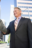 Two businessmen shaking hands, outdoors