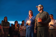 Wife and husband, Kate Walker and Randy Smith, host family to German exchange student, Diren Dede, hold hands while speaking at Dede's vigil on May 2, 2014, at the Fort Missoula soccer field where Dede played.