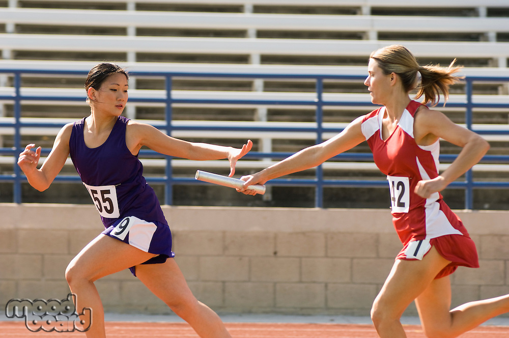 Female track athlete passing relay baton to another one