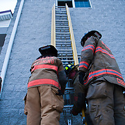 Fire fighters adjust a heavy 35 foot fiberglass ladder during ladder training Wednesday, July 6, 2011, in Camden-Wyoming Delaware.