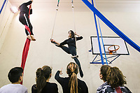 """NAPLES, ITALY - 16 MARCH 2018: Aerial Dance instructor Caterina Spezzaferri (29) teaches aerial dance to teenagers at """"Il Tappeto di Iqbal"""" (Iqbal's carpet), a non-profit cooperative in Barra, the estern district of Naples, Italy, on March 16th 2018.<br /> <br /> Il Tappeto di Iqbal (Iqbal's Carpet) is a non-profit cooperative founded in 2015 and Save The Children partner since 2015 that operates in the Naple's eastern neighborhood of Barra children in the arts of circus, theater and parkour. It was named after Iqbal Masih, a Pakistani boy who escaped from life as a child slave and became an activist against bonded labor in the 1990s.<br /> Barra, which is home to some 45,000 people, has the highest rate of school dropouts in the Italian region of Campania. Once a thriving industrial community, many of the factories were destroyed in a 1980 earthquake and never rebuilt. The resulting de-industrialization turned Barra into a poor, decaying neighborhood. There are no cinemas, theaters, parks or public spaces in Barra.<br /> The vast majority of children from poor families are faced with the choice of working in the black economy or joining the ranks of the organised crime.<br /> Recently, Save the Children Italy opened a number of educational and social spaces in Barra. The centers, known as Punti Luce, or points of light, aim to help local kids stay out of the ranks of the organised crime and have also become hubs for Iqbal's Carpet to work."""