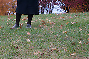 Woman pictured in black skirt and black tights standing on a hill surrounded by fallen leaves.