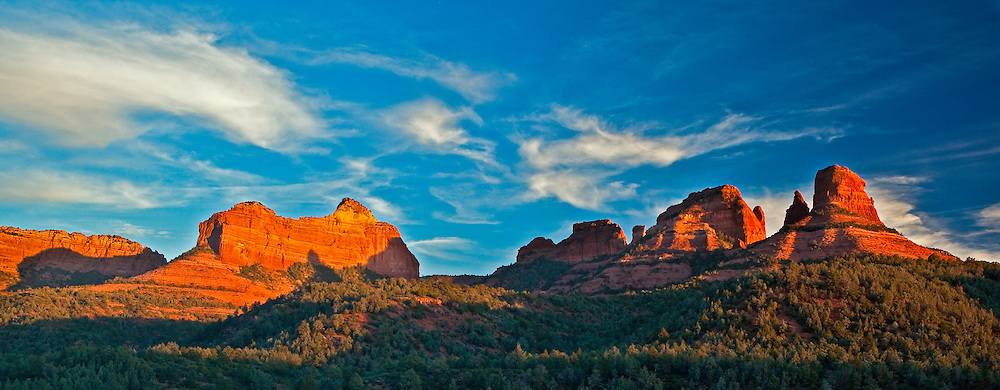 The evening sun sets on the surrounding red rock next to Oak Creek Canyon, near Sedona, Arizona.