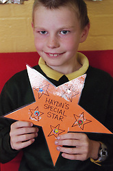 Primary school boy holding up prize star smiling,
