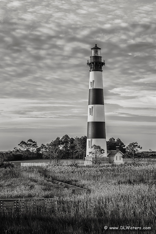 """Black-and-white portrait of bodie Island Lighthouse. Bodie Island Lighthouse stands 156 feet tall and the height of each stripe is 22 feet. It is thought that the island got its name because of the many bodies that washed up from shipwrecks. The inside plaque reads, """"Body Island"""". no one is certain how the spelling change came about."""