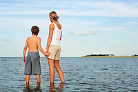 Mother and Son standing in water by shore of Beach looking at view back view