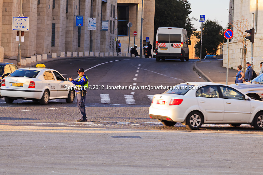 A police officer directs traffic at a busy intersection in downtown Jerusalem. WATERMARKS WILL NOT APPEAR ON PRINTS OR LICENSED IMAGES.