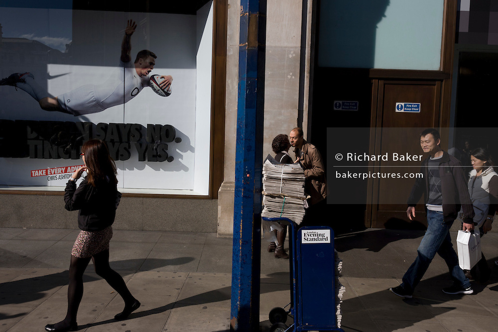 A diving England rugby player spreads across the Nike shop window at Oxford Circus, in front of kissing passers-by.