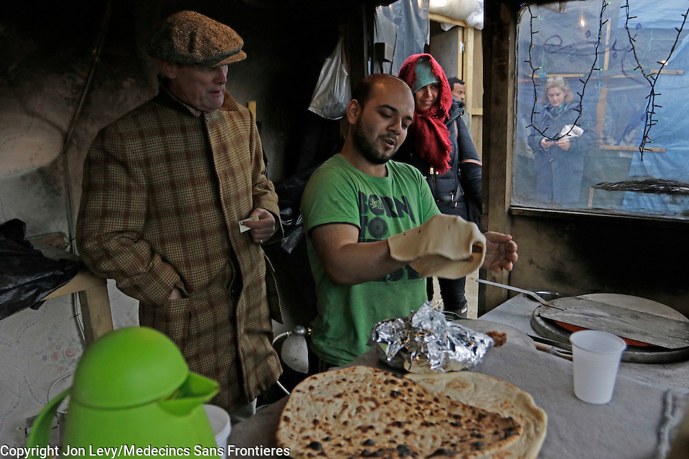Writer AA Gill watches a baker from Barri Italy make naan bread in a small make-shift bakery in the refugee camp in Calais France. <br />