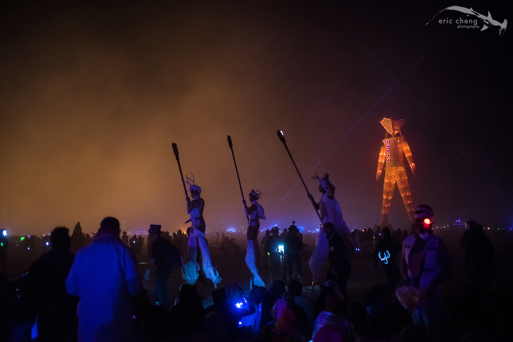 Pre-burn ceremony, featuring stilt walkers carrying torches (in the dust storm). Burning Man 2014.