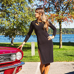 A young lady in a black dress, standing with her hand on a red Mustang.