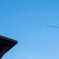 "An airplane with a banner reading ""Big Hickup in 2020: Jetgate Scandal"" flies over a rally for Democratic presidential candidate and former Colorado Governor John Hickenlooper at the Greek Amphitheater in Denver's Civic Center Park on Thursday, March 7, 2019. Photo by Andy Colwell, special to the Colorado Sun"