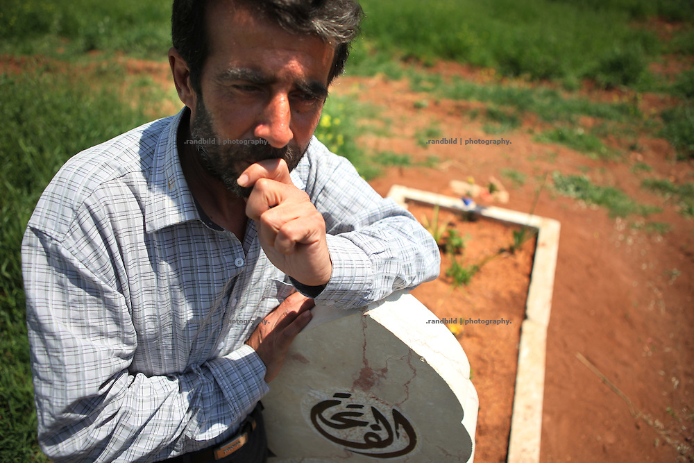 Shakib Ghasal stands at the grave of his Son who is the first killed in the uprising in Taftanaz on August 9, 2011. Taftanaz northeast of Idlib city was seriouosly attacked in April by helicopters from a nearby air base. dozens of houses were bombed to the ground and many peolpe were killed as well.