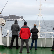 A small group of passengers stands on the deck of an Antarctic cruise ship to look at the first land sighted after crossing Drake's Passage. The island in the distance is part of the South Shetland Islands along English Strait and Robert Island just off the Antarctic Peninsula.