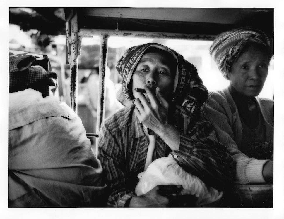 Burmese woman draws on her cheroot waiting for the pick up truck to leave from Nyaung U, Burma (Myanmar).