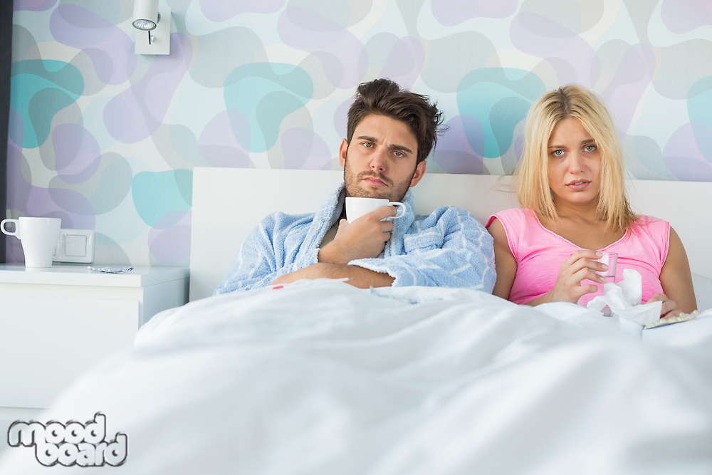 Portrait of sad couple holding coffee mug and glass while relaxing on bed