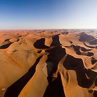 Africa, Namibia, Namib Naukluft National Park, Aerial view of morning sun lighting towering sand dunes in Namib Desert near Sossusvlei