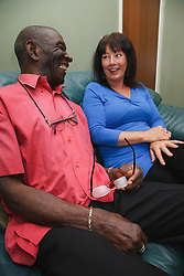 Elderly black man with white woman carer at home chatting