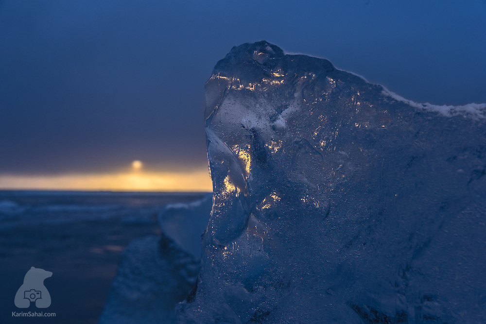 The setting sun shines through a large piece of clear ice, on the black sand beach near Jökulsárlón, the large glacial lake at the edge of Iceland's Vatnajökull National Park. Hundreds of magnificent pieces of clear ice like this one find their way to the beach when they detach themselves from lager icebergs that float in the nearby lake.