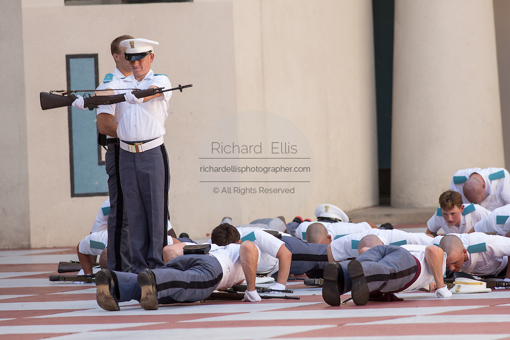 Members of the Citadel Military College corps of cadets are penalized for sloppy marching with push ups following the first Friday Dress Parade on September 6, 2013 in Charleston, South Carolina. The Friday Dress Parade is a tradition at the Citadel going back to 1843.