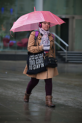 © Licensed to London News Pictures. 14/05/2015. Bristol, UK. A woman with an umbrella carrying a bag with the slogan 'I didn't want to go outside, but my hair looked too good to stay in'. She was among many braving the wet weather in Bristol city centre today, Thursday 14th May 2015. Photo credit : Rob Arnold/LNP