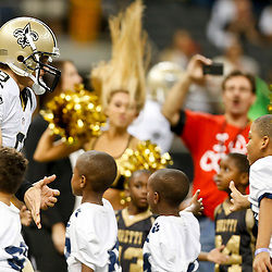 Aug 16, 2013; New Orleans, LA, USA; New Orleans Saints quarterback Drew Brees (9) runs past youth football players in the Heads Up program prior to kickoff against the Oakland Raiders in a preseason game at the Mercedes-Benz Superdome. Mandatory Credit: Derick E. Hingle-USA TODAY Sports